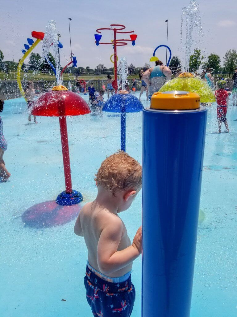 a boy standing at the turkey brook park pirates cove water park surrounded by bright red blue and yellow water fixtures