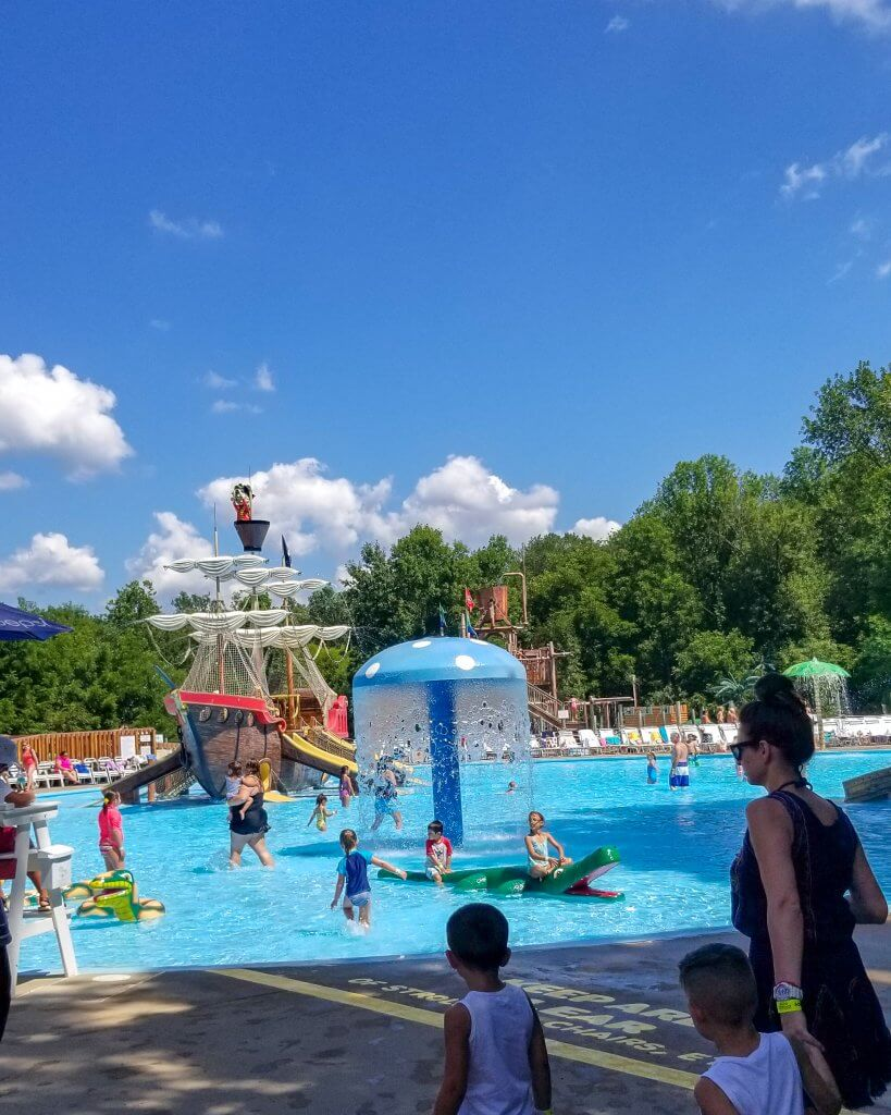 a blue sky over a pirate themed splash pag and wading pool at land of make believe nj