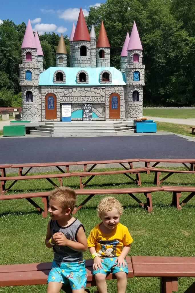 the castle stage at the land of make believe on green grass with a black stage and two little boys sitting on wooden bleachers in front