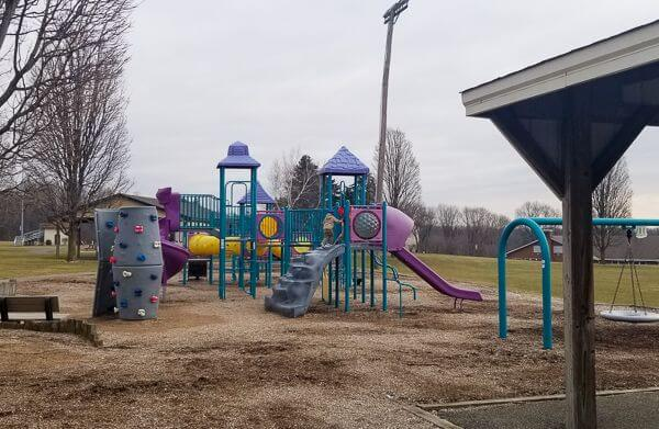 A blue and purple play ground and rock pring park showing the area for the big kids