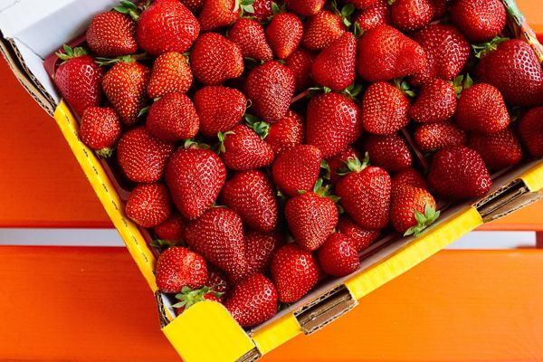 a pallet of bright red pick your own strawberries from NJ in a yellow box on an orange table.