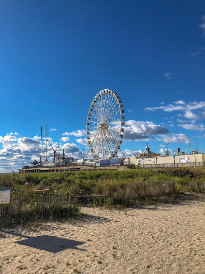 photo of the ferris wheel on the atlantic city boardwalks in NJ from the beach with a bright blue sky