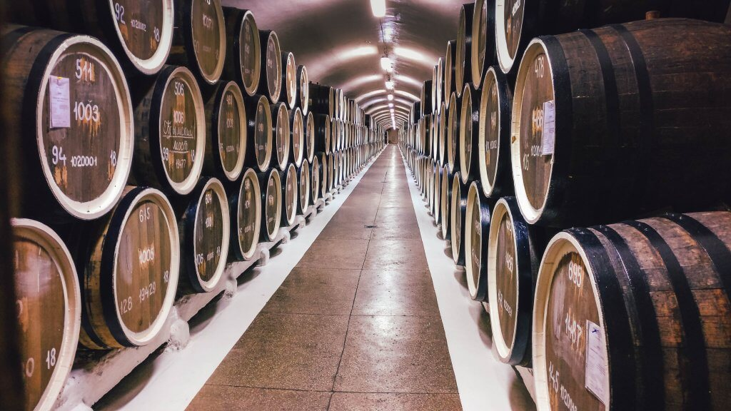 barrels of wine lining a winery storage
